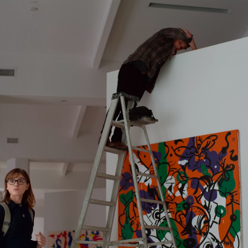 image from 'Velvet Buzzsaw' (2019) of art installer on top of ladder above piece of artwork